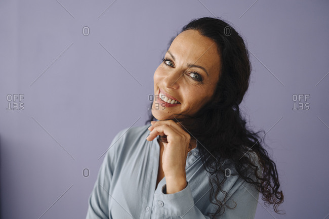 Close-up of happy mid adult woman with wavy hair against purple background
