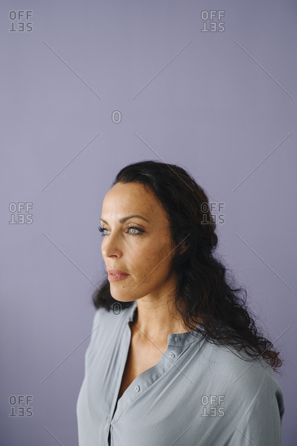 Close-up of thoughtful beautiful woman looking away against purple background