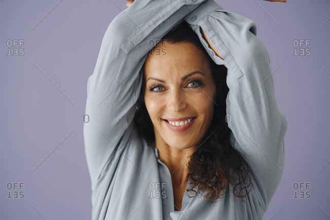 Close-up of smiling mid adult woman with arms raised against purple background