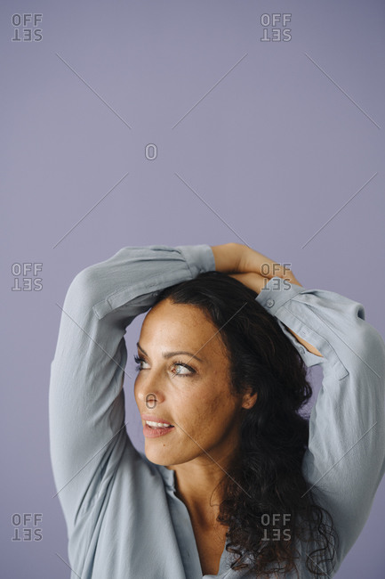Close-up of mid adult woman with arms raised looking away against purple background