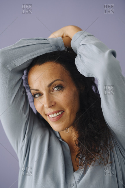 Close-up of smiling beautiful woman with arms raised against purple background