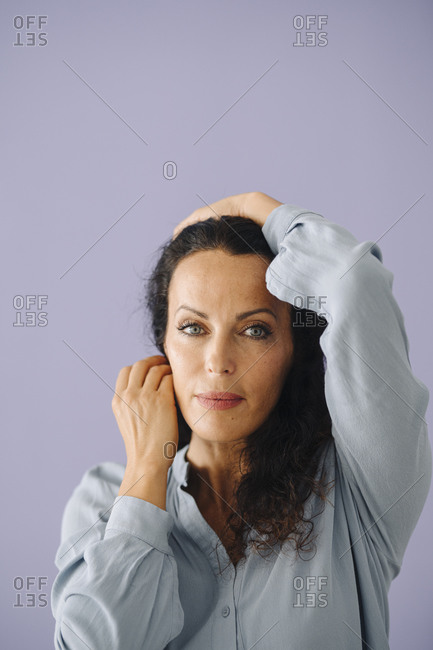 Close-up of confident mid adult woman posing against purple background