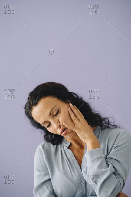 Mid adult woman with eyes closed making face against purple background