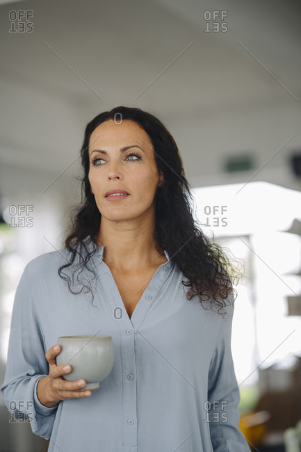 Female owner holding coffee mug looking away while standing in cafe