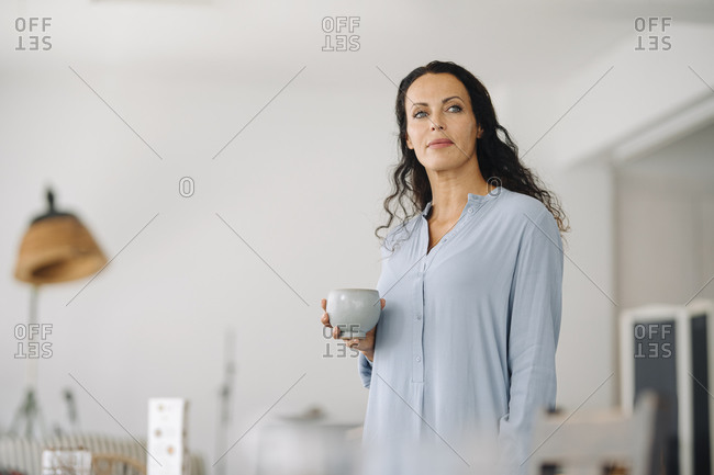 Thoughtful female owner holding coffee mug while standing in cafe