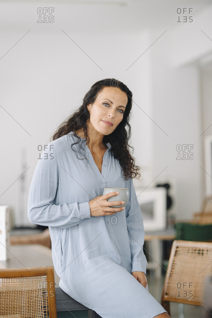 Female owner holding coffee mug while sitting on table in restaurant