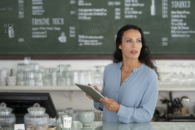 Female owner using digital tablet looking away while standing by counter in cafe