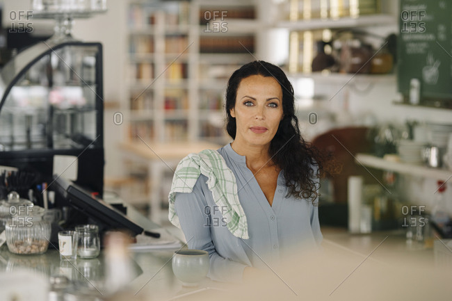 Confident female owner standing at counter in coffee shop