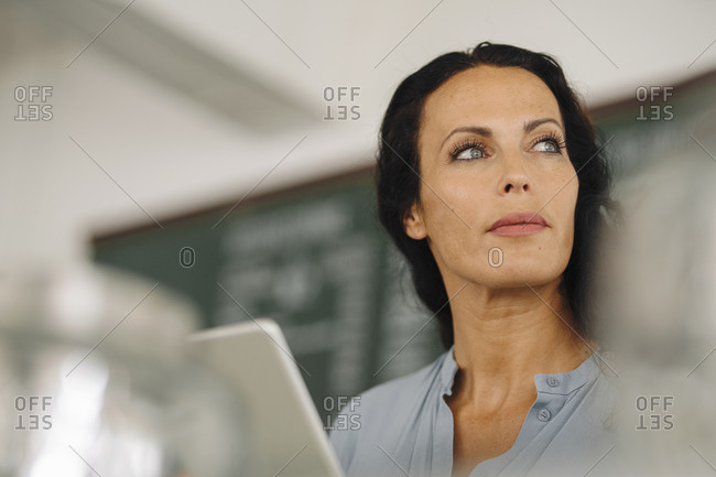 Close-up of thoughtful female barista looking away in coffee shop