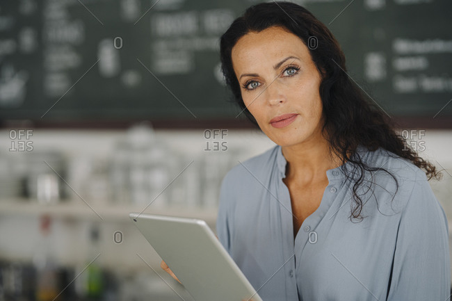 Confident female barista holding digital tablet while working in cafe