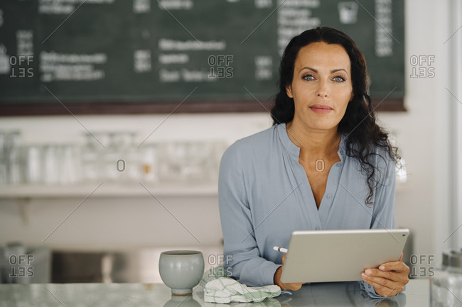 Confident female barista using digital tablet on counter while standing in restaurant