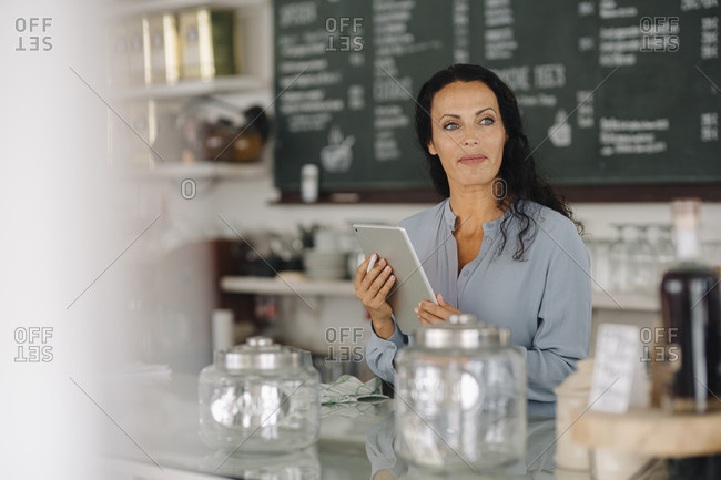 Smiling female owner holding digital tablet contemplating while standing in cafe