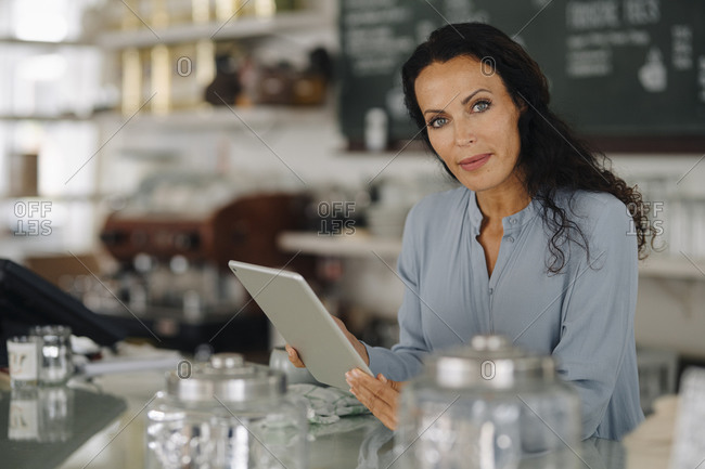 Confident female owner using digital tablet while standing at counter in restaurant