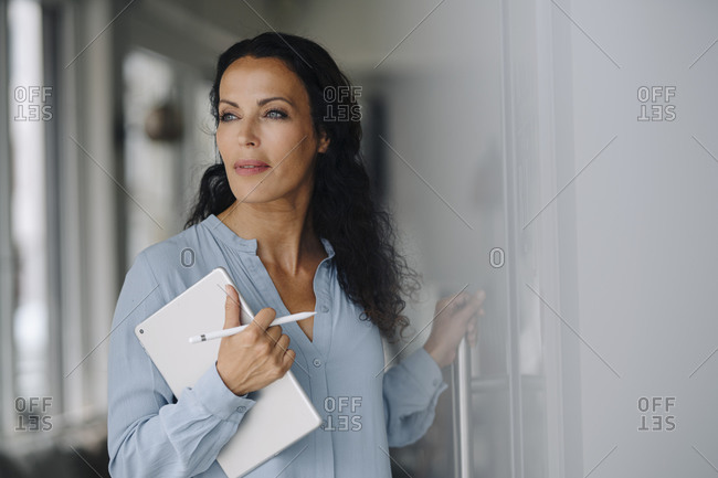 Female owner with digital tablet looking away while standing at entrance of coffee shop