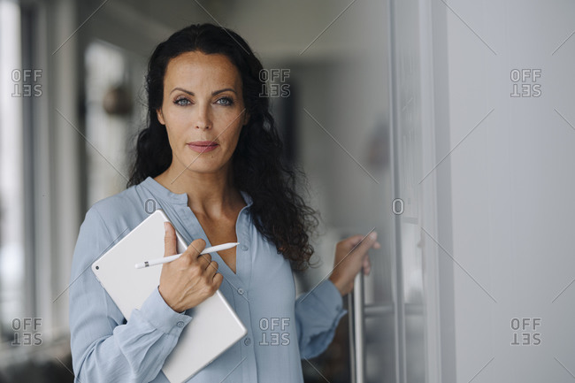 Female owner holding digital tablet standing at entrance of coffee shop