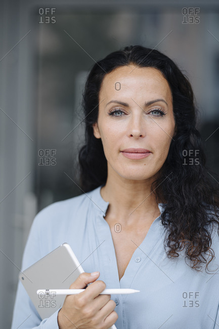 Close-up of female owner with gray eyes holding digital tablet outside coffee shop