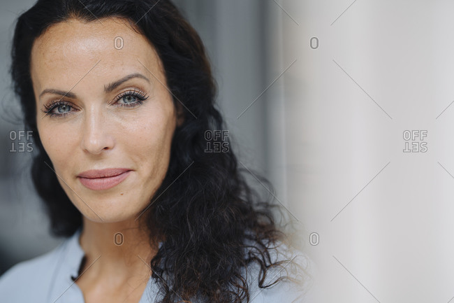 Close-up of confident woman with gray eyes outside cafe