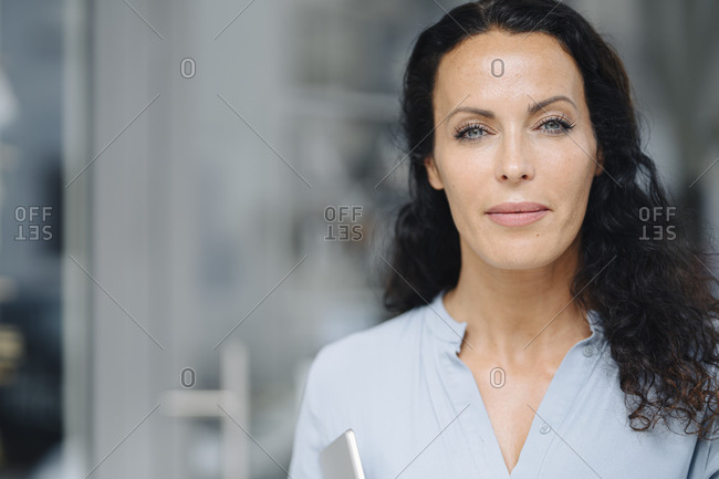 Close-up of confident female barista with gray eyes outside cafe