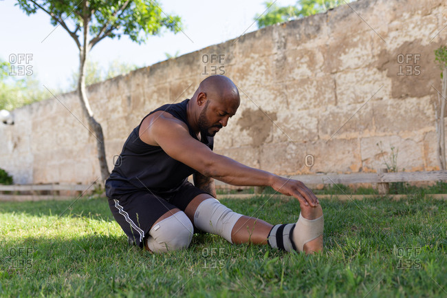 Mature man with shaved head exercising on grassy land against wall in yard