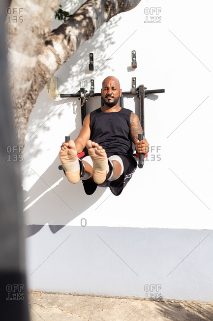 Bald mature man exercising on equipment against wall in yard during sunny day