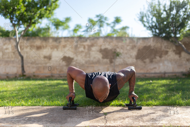 Mature man with shaved head practicing push-ups on grassy land in yard