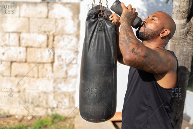 Bald mature man drinking water while standing by punching bag in yard