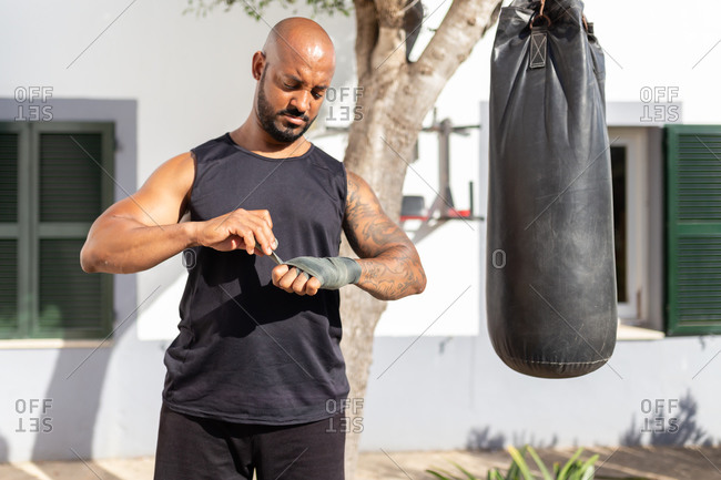 Bald mature man tying bandage on hand while standing by punching bag in yard