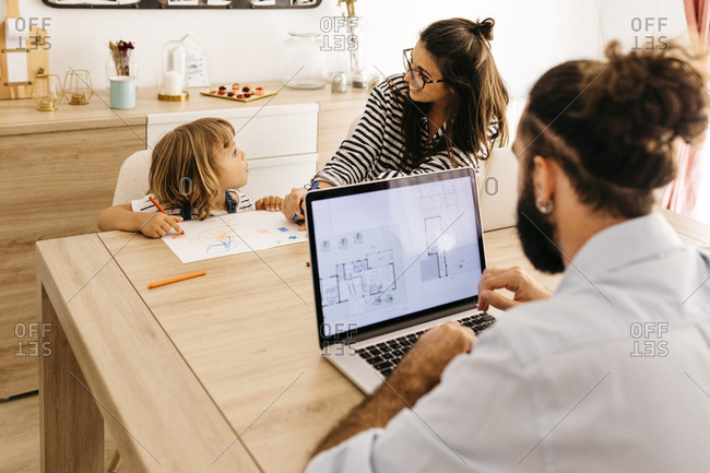Man using laptop while mother and daughter painting in dining room