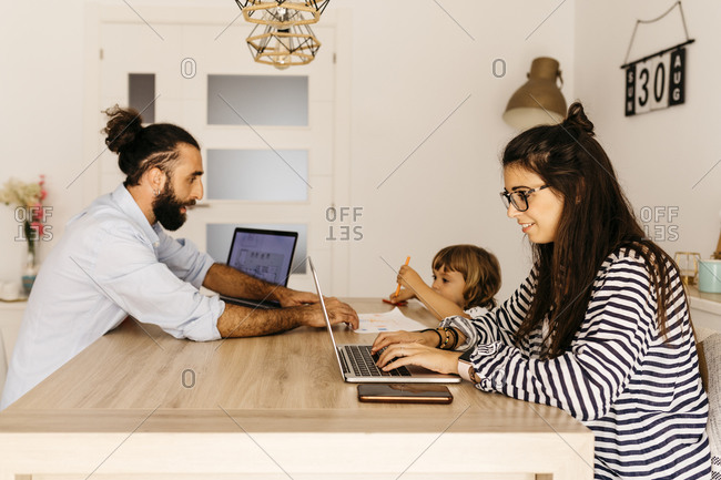 Woman working over laptop while father and daughter painting on dining table at home