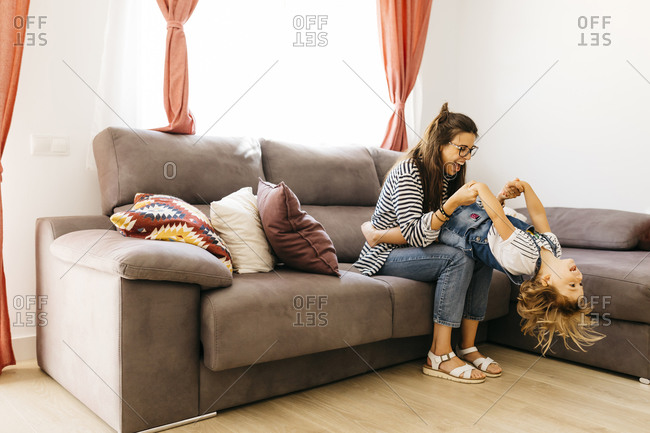 Happy mother and daughter playing on sofa at home