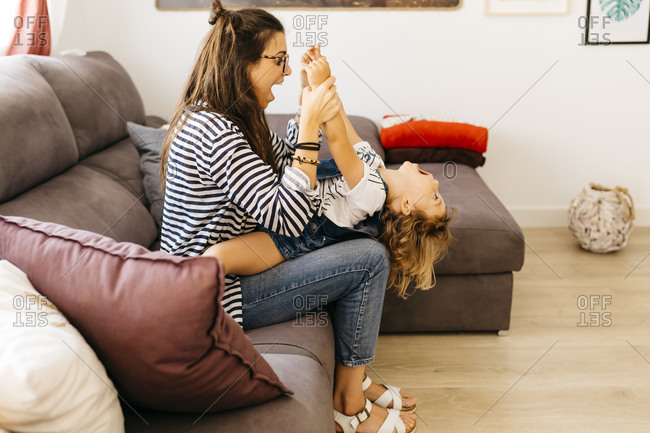 Mother with mouth open holding playful daughter's hands while sitting with her on sofa at home