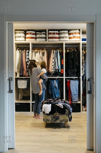 Mother with daughter choosing clothes in dressing room at home seen through doorway