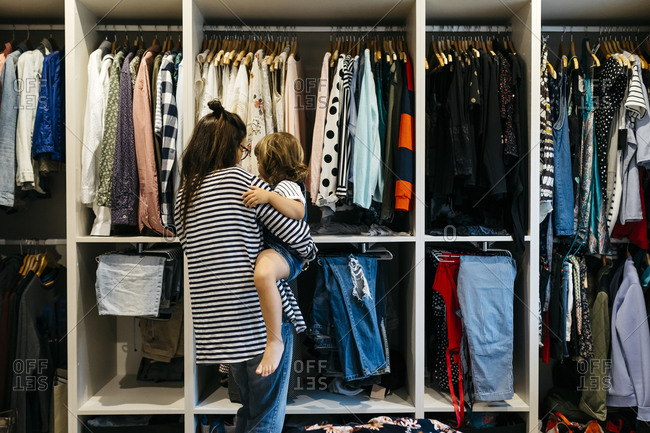 Mother carrying daughter while choosing clothes in dressing room at home
