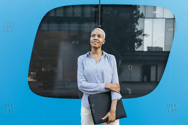 Businesswoman looking away while standing against blue wall