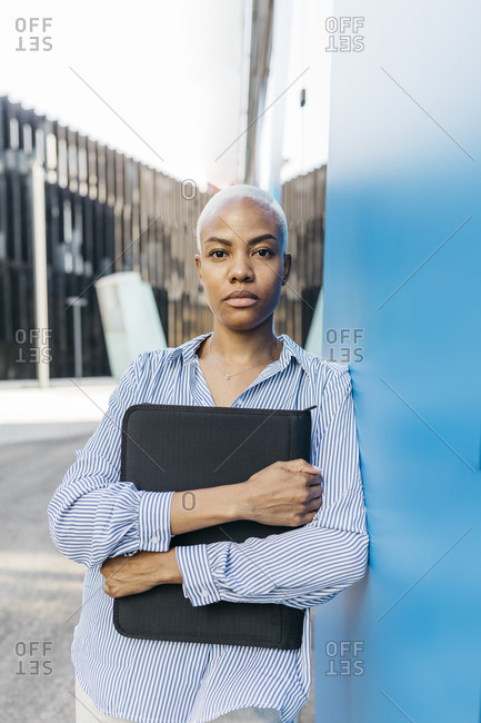 Businesswoman with folder standing by blue wall in city