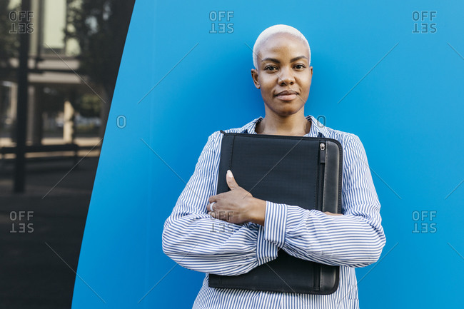 Confident businesswoman with folder standing against blue wall