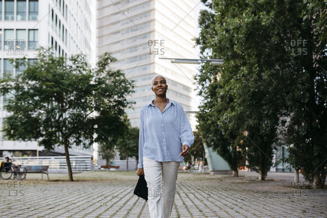 Smiling businesswoman with file walking in city