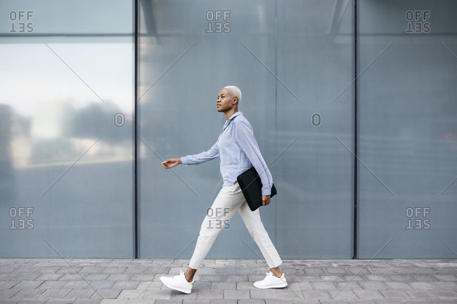 Businesswoman with folder walking against building in city