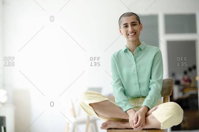 Portrait of a smiling woman sitting on chair in a loft