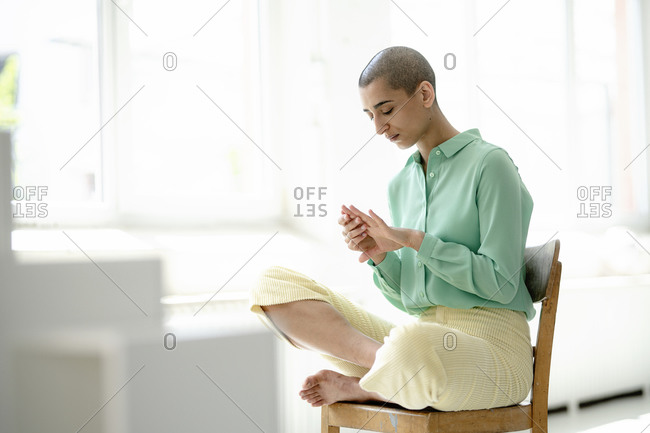 Woman sitting on chair in a loft looking at her hand
