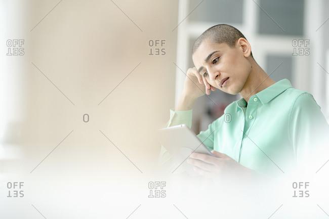 Focused businesswoman using tablet in loft office