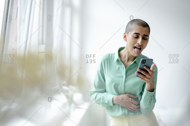 Woman in a loft using smartphone sticking out her tongue