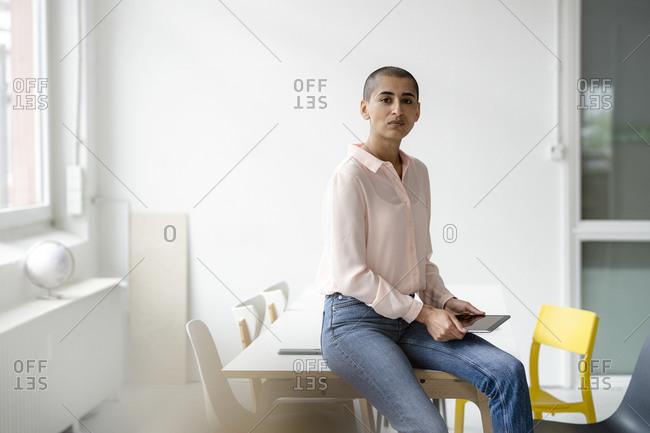 Portrait of businesswoman sitting on desk in loft office holding tablet