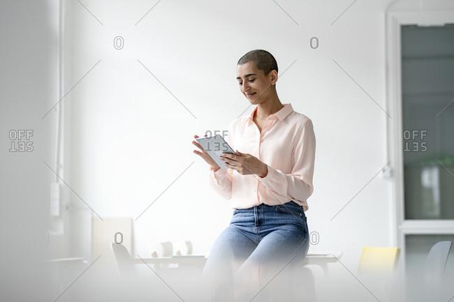 Businesswoman sitting on desk in loft office using tablet
