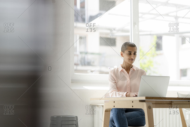 Businesswoman using laptop at desk in loft office