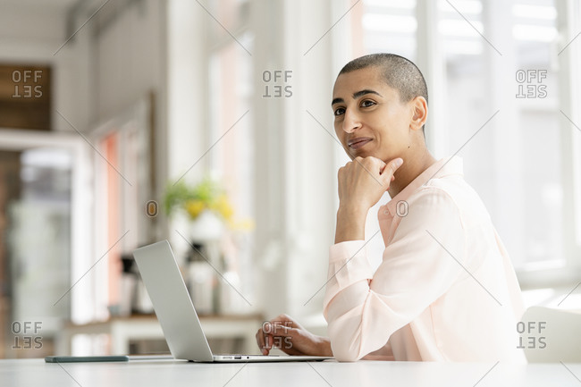 Smiling businesswoman using laptop at desk in loft office