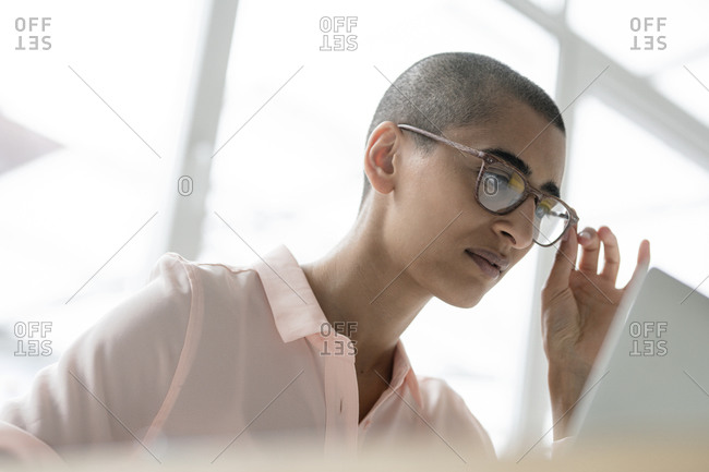 Portrait of businesswoman with glasses using laptop