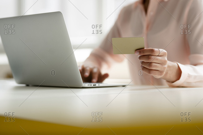 Close-up of businesswoman holding credit card and using laptop at desk in office