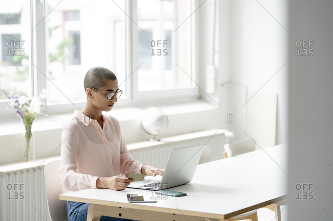 Businesswoman holding credit card and using laptop at desk in loft office
