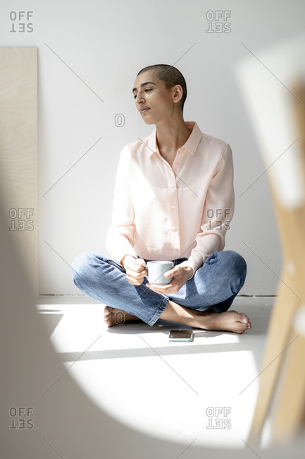 Portrait of a thoughtful woman sitting on the floor in a loft